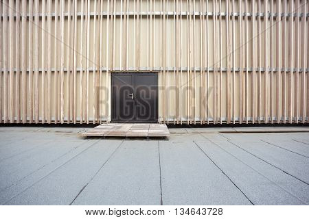 The wall is lined with unpainted wood and an black door