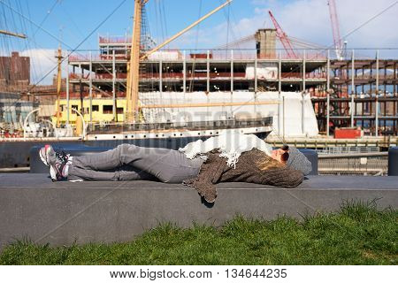 NEW YORK - MARCH 17, 2016: woman take a rest at Pier 15 at daytime. Pier 15 is located east of South Street and FDR Drive in Lower Manhattan, New York City.