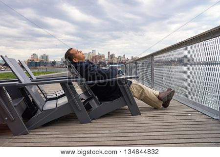 NEW YORK - MARCH 17, 2016: man sit in the armchair at Pier 15 at daytime. Pier 15 is located east of South Street and FDR Drive in Lower Manhattan, New York City.