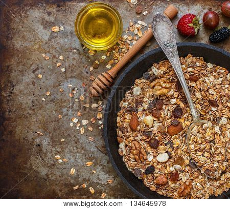 Homemade granola with raisins walnuts almonds and hazelnuts. Muesli and honey. Healthy Breakfast. Top view. Copy space