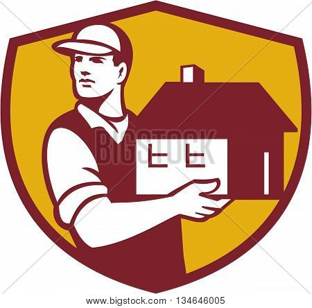Illustration of a house mover handling holding house looking to the side set inside shield crest on isolated background done in retro style.