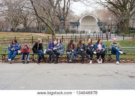 NEW YORK - CIRCA MARCH, 2016: people sit on the bench in Central Park. Central Park is an urban park in middle-upper Manhattan, within New York City.