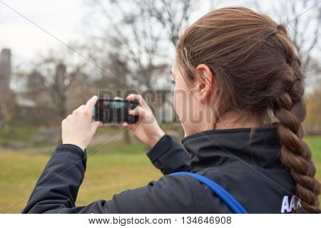 NEW YORK - CIRCA MARCH, 2016: young woman taking photo in Central Park. Central Park is an urban park in middle-upper Manhattan, within New York City.
