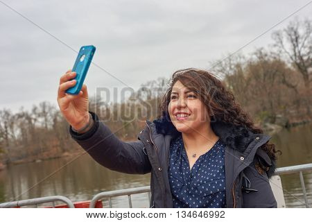 NEW YORK - CIRCA MARCH, 2016: woman taking selfie in Central Park. Central Park is an urban park in middle-upper Manhattan, within New York City.