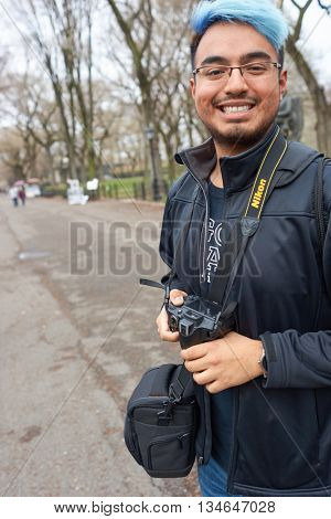 NEW YORK - CIRCA MARCH, 2016: outdoor portrait of young man with Nikon camera. Nikon, is a Japanese multinational corporation headquartered in Tokyo, Japan, specializing in optics and imaging products