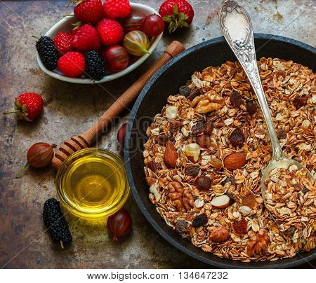 Homemade granola with raisins walnuts almonds and hazelnuts. Muesli and honey . Fresh berries - raspberry strawberry gooseberry mulberry. Healthy Breakfast