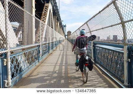 NEW YORK - CIRCA MARCH, 2016: cyclist crosses the Manhattan Bridge in New York. The Manhattan Bridge is a suspension bridge that crosses the East River in New York City,