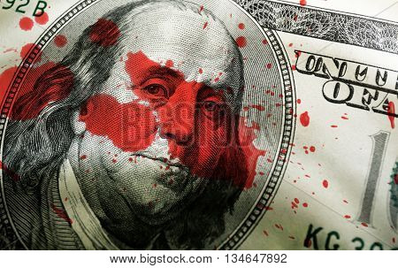 Dollar face and blood splashes close-up