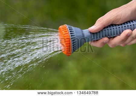 hand watering garden with sprinkler on blurred background closeup