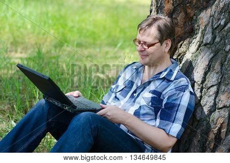 Man with laptop is resting in forest near large trunk of old pine tree