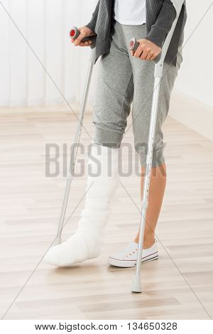 Close-up Of Woman Leg In Plaster Cast Using Crutches While Walking