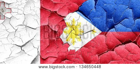 Malta flag with Philippines flag on a grunge cracked wall