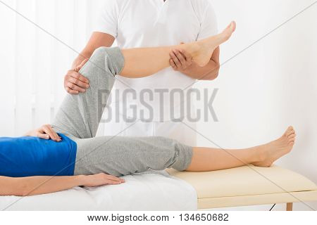 Close-up Of Masseur Giving Leg Massage To Woman In Spa Saloon