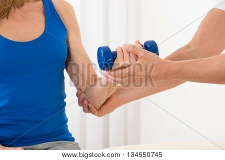 Close-up Of Instructor Assisting Woman For Exercising With Blue Dumbbell