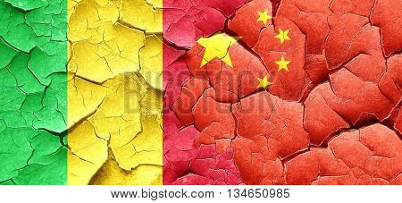 Mali flag with China flag on a grunge cracked wall