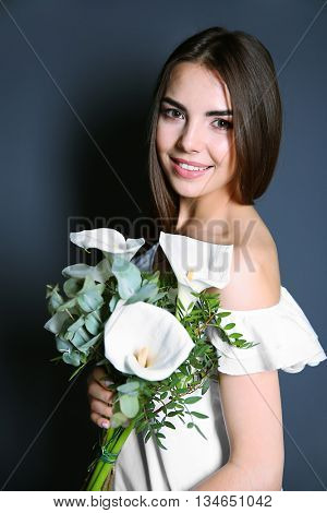 Beautiful young woman holding bouquet on dark background