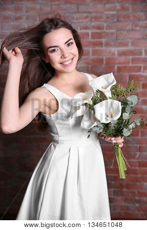 Beautiful young woman holding bouquet on red brick wall background