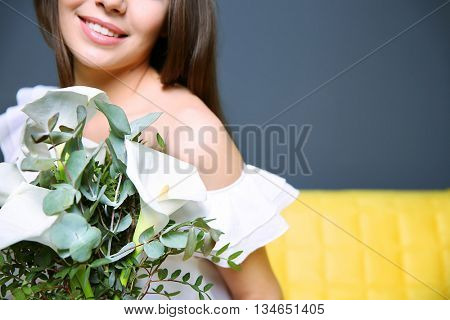 Beautiful young woman holding bouquet, close up