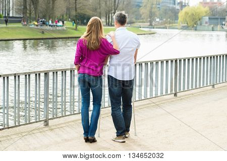 Woman With Her Disabled Husband Looking At Lake