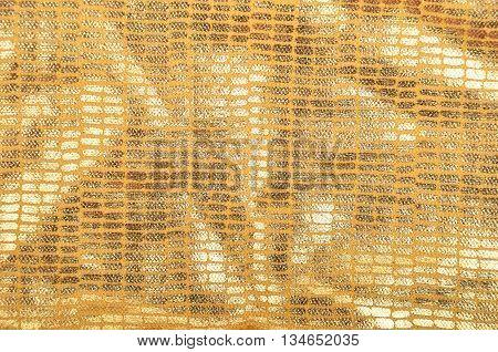 Golden textured brocade cloth background close up
