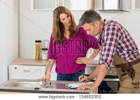 Woman Looking At Male Plumber Writing On Clipboard In Kitchen