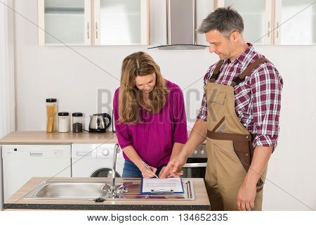 Happy Woman Signing Invoice From Male Plumber In Kitchen