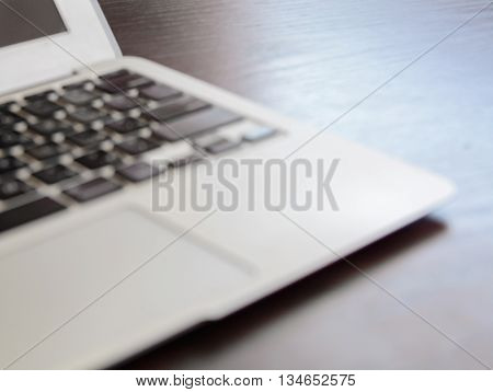 Workplace with open laptop on black modern wooden desk, soft focus