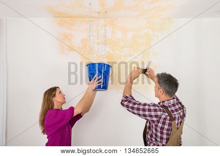 Male Worker Photographing Water Damaged Ceiling While Woman Collecting Water In Bucket