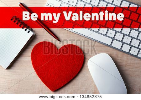 Computer peripherals with red heart, pen and notebook on light wooden table and text Be my Valentine