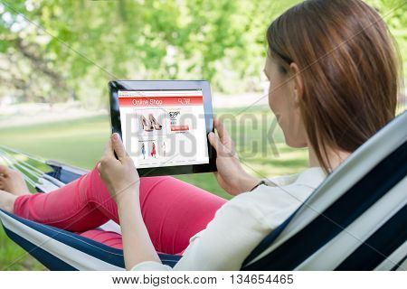Young Woman Lying In Hammock Shopping Online With Digital Tablet