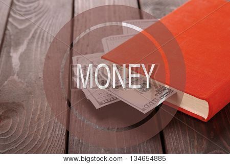 Money sign. Red book with nested dollar banknotes on wooden table.