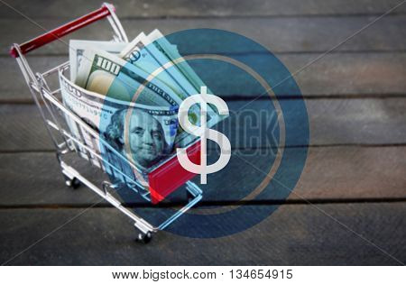 Dollar icon. Small shopping trolley with dollars banknotes on wooden background
