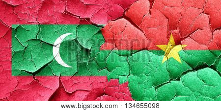 Maldives flag with Burkina Faso flag on a grunge cracked wall