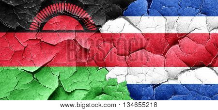 Malawi flag with Costa Rica flag on a grunge cracked wall