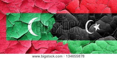Maldives flag with Libya flag on a grunge cracked wall