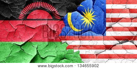 Malawi flag with Malaysia flag on a grunge cracked wall