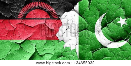 Malawi flag with Pakistan flag on a grunge cracked wall