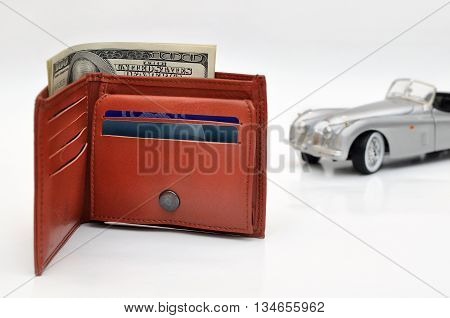 closeup Wallet with US Dollars and blured old toy car background