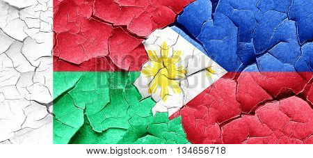 Madagascar flag with Philippines flag on a grunge cracked wall