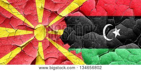 Macedonia flag with Libya flag on a grunge cracked wall