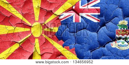 Macedonia flag with Cayman islands flag on a grunge cracked wall
