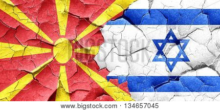 Macedonia flag with Israel flag on a grunge cracked wall