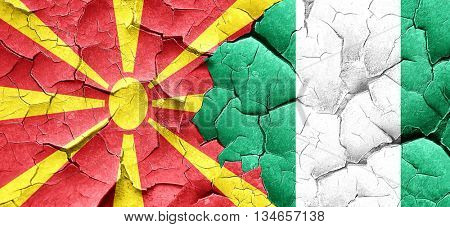 Macedonia flag with Nigeria flag on a grunge cracked wall