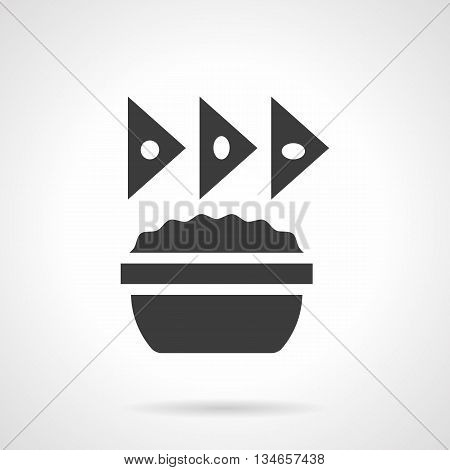 Monochrome silhouette of bowl with sauce and triangle cheese chips. Appetizer menu with nachos. Mexican food. Symbolic black glyph style vector icon.