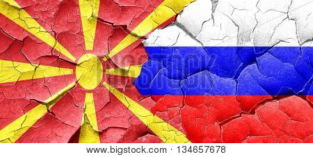 Macedonia flag with Russia flag on a grunge cracked wall
