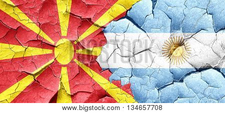 Macedonia flag with Argentine flag on a grunge cracked wall