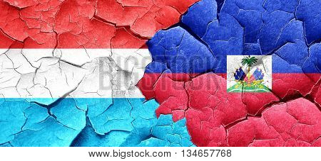 Luxembourg flag with Haiti flag on a grunge cracked wall