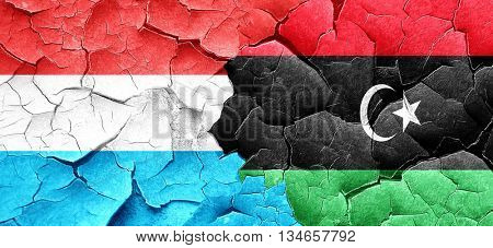 Luxembourg flag with Libya flag on a grunge cracked wall