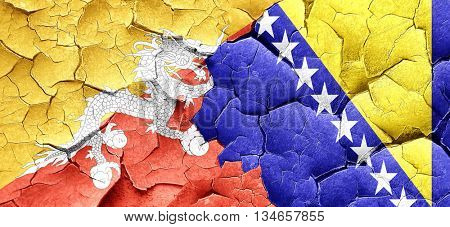 Bhutan flag with Bosnia and Herzegovina flag on a grunge cracked
