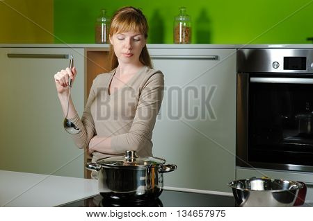 Girl on kitchen with a ladle. Smiling redhead woman with ladle cooking soup in home kitchen. Person removing lid from cooking pot. Beautiful young housewife looking in to pan.